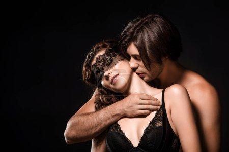 Photo pour Portrait d'homme étreindre et embrasser une amie torse nue sexy avec dentelle noire sur yeux isolée sur fond noir - image libre de droit