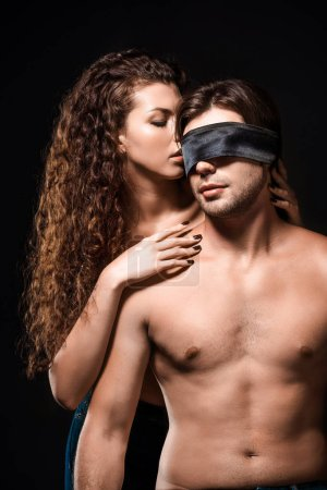 portrait of woman hugging shirtless boyfriend with silk ribbon on eyes isolated on black
