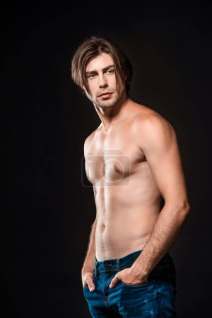 portrait of pensive shirtless man in jeans looking away isolated on black