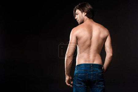 Photo for Back view of young shirtless man in jeans looking away isolated on black - Royalty Free Image