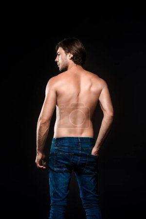 rear view of shirtless man in jeans looking away isolated on black