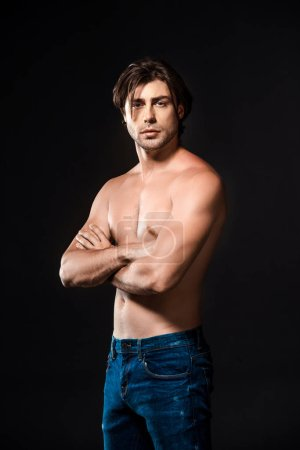 portrait of handsome shirtless man with arms crossed looking at camera isolated on black