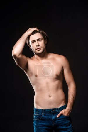 portrait of handsome shirtless man in jeans looking at camera isolated on black