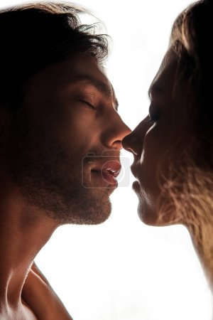 side view of couple kissing while standing face to face, isolated on white