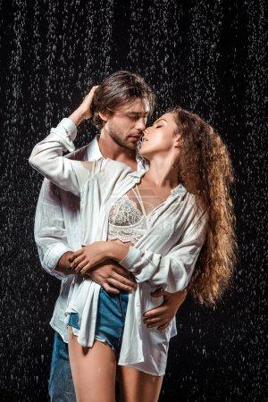 Photo for Portrait of seductive couple hugging under rain isolated on black - Royalty Free Image