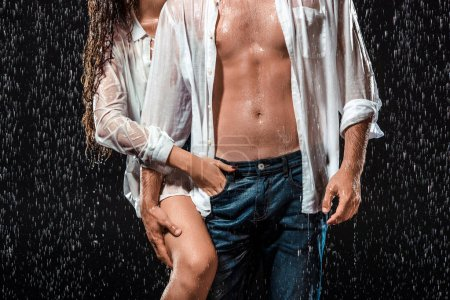 partial view of sexy couple in white shirts standing under rain isolated on black