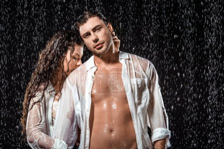 Photo for Sexy couple in white shirts standing under rain isolated on black - Royalty Free Image