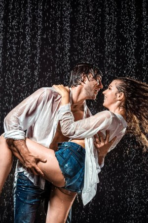 happy wet couple in white shirts standing under rain isolated on black