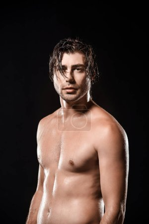 portrait of shirtless man with wet hair looking at camera isolated on black