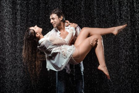 young man holding girlfriend in white shirt while standing under rain isolated on black