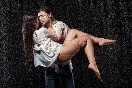 junger Mann hält Freundin im weißen Hemd im Regen isoliert auf schwarz
