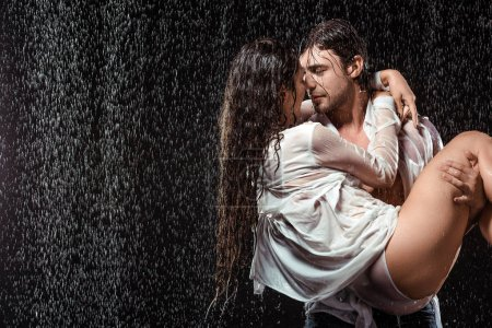 Photo for Portrait of young man holding girlfriend in white shirt while standing under rain isolated on black - Royalty Free Image