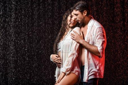 Photo pour Portrait de couple sexy en chemises blanches debout sous la pluie sur fond noir - image libre de droit