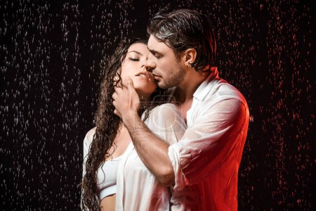 Photo for Portrait of sexy couple in white shirts standing under rain on black backdrop - Royalty Free Image