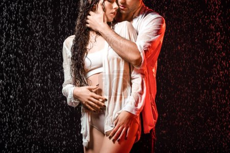 partial view of sexy couple in white shirts standing under rain on black backdrop