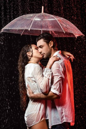 side view of romantic couple in white shirts with umbrella standing under rain on black backdrop