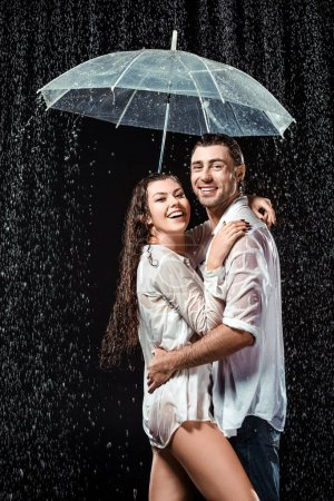 side view of happy couple in white shirts standing under umbrella under raindrops isolated on black