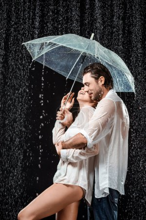 Photo for Side view of romantic couple in white shirts standing under umbrella under raindrops isolated on black - Royalty Free Image