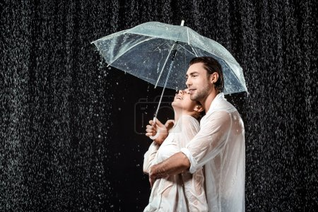 side view of romantic couple in white shirts standing under umbrella under raindrops isolated on black