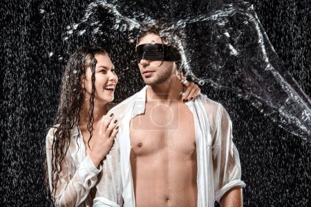 portrait of man with black ribbon on eyes and smiling girlfriend while swilled with water isolated on black