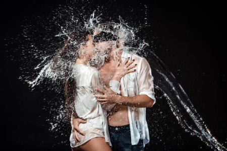 portrait of man with black ribbon on eyes hugging sexy girlfriend near by while swilled with water isolated on black