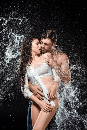 portrait of sexy young couple with water splash isolated on black