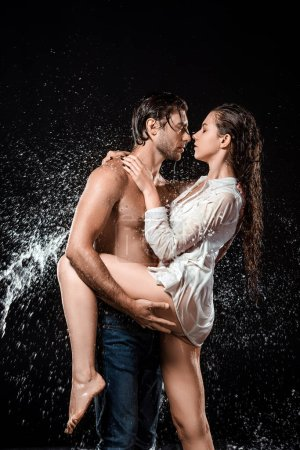 side view of sexy young couple swilled with water isolated on black