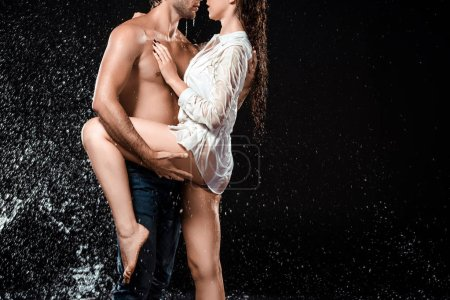 cropped shot of seductive couple swilled with water isolated on black