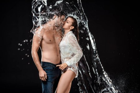 side view of seductive couple swilled with water isolated on black