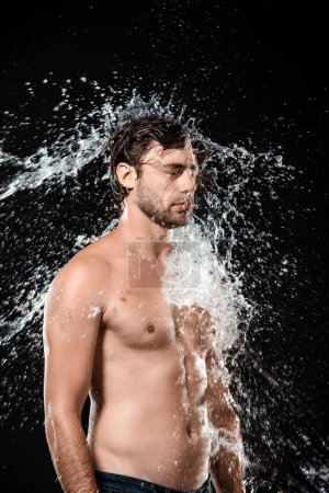 side view of young man with water splash isolated on black
