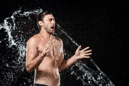 side view of emotional young man swilled with water isolated on black