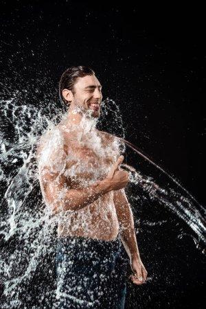 souriant jeune homme montrant pouce vers le haut tandis que la maison avec eau splash isolé sur fond noir