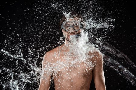 portrait of shirtless man in swimming mask with snorkel swilled with water splash isolated on black
