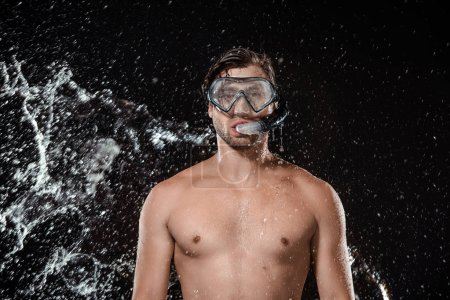 portrait of shirtless man in swimming mask with snorkel swilled with water isolated on black