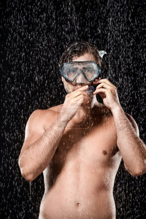 portrait of shirtless man in swimming mask with snorkel standing under water drops isolated on black