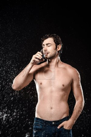portrait of shirtless man drinking water from glass while swilled with water isolated on black