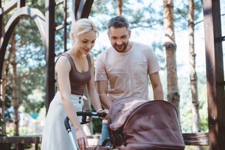 parents looking at baby pram in park