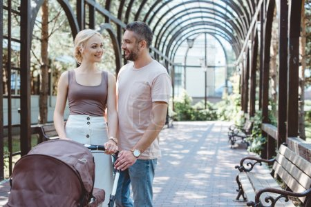Foto de Padres alegres caminando con el carro de bebé en el parque y mirando el uno al otro - Imagen libre de derechos