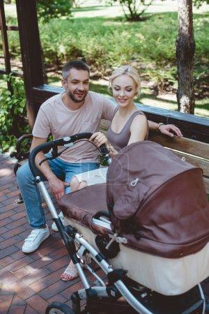 Foto de Padres sentados en la banca cerca de carro de bebé y mirando al niño en el Parque - Imagen libre de derechos