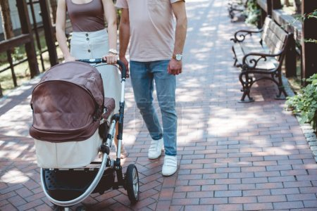 Photo for Cropped image of parents walking with baby carriage in park - Royalty Free Image