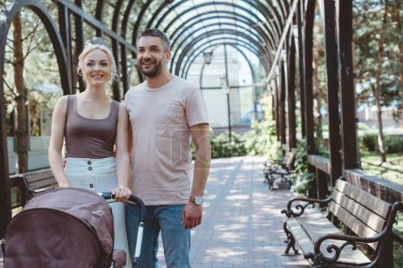 Foto de Sonriendo a los padres con carro de bebé en el parque de pie y mirando a - Imagen libre de derechos