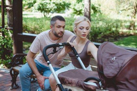 Foto de Padres sentados en el Banco y mirando el carro de bebé en el Parque - Imagen libre de derechos