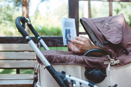 Photo for Cropped image of man holding cigarette and business newspaper in baby carriage - Royalty Free Image