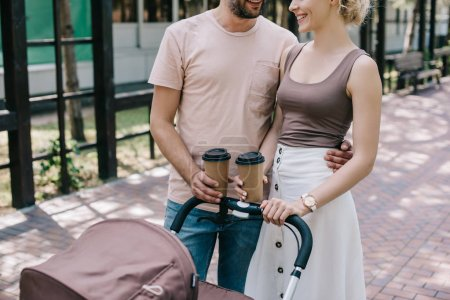 Foto de Recortar imagen de padres con café para ir cerca del carro de bebé en el Parque - Imagen libre de derechos