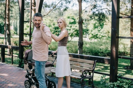 father talking by smartphone near baby carriage in park, angry mother touching him