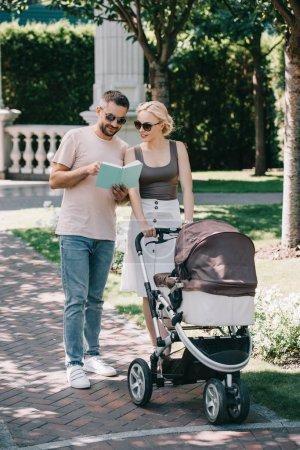 parents permanent avec Landau en parc et en regardant de livre