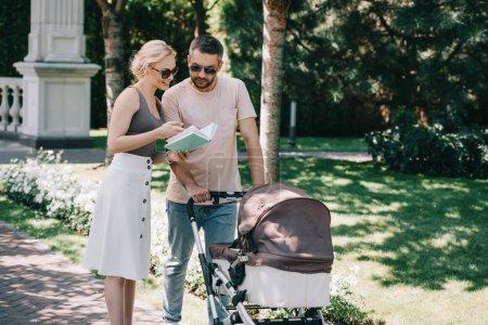 Foto de Madre y padre de pie cerca del carro de bebé en el parque y sosteniendo libro - Imagen libre de derechos