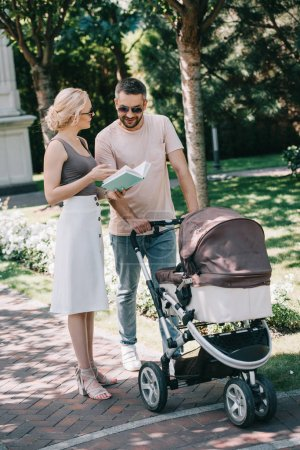Photo for Smiling parents standing near baby carriage in park and holding book - Royalty Free Image