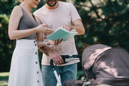 Foto de Imagen recortada de los padres junto a carro de bebé en el parque y leyendo el libro - Imagen libre de derechos