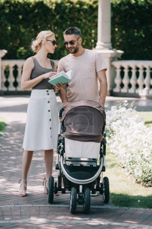 Foto de Padres junto a carro de bebé en el parque y sosteniendo libro - Imagen libre de derechos